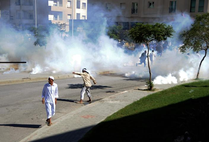 """Demonstrators throw stones during a protest against the anti-Islam film """"Innocence of Muslims"""" outside the U.S. Embassy in Tunis, Tunisia, as police respond with tear gas Friday, Sept. 14, 2012. Protests against he film spread to their widest extent yet around the Middle East and other Muslim countries Friday, as protesters smashed into the German Embassy in the Sudanese capital and security forces in Egypt and Yemen fired tear gas and clashed with protesters to keep them away from U.S. embassies. (AP Photo/Hassene Dridi)"""