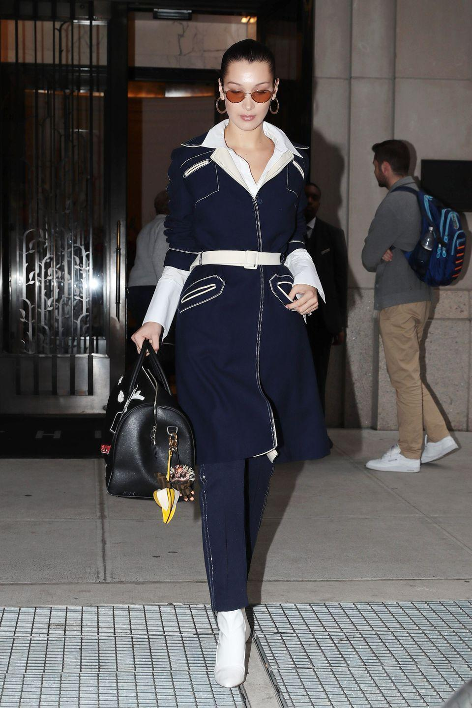 <p>In a navy coat, white belt, metallic-striped track pants, white leather boots by Stuart Weitzman, black leather duffle bag, and tinted sunglasses while out in New York.</p>