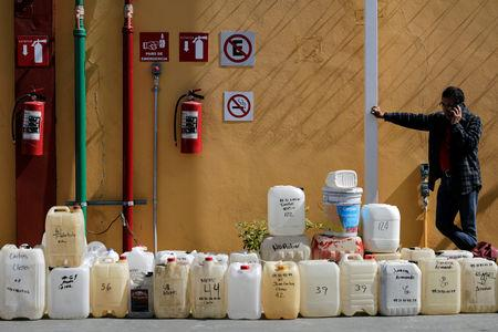 A man talks on a mobile phone while standing next to empty containers lined up at a gas station in Morelia, Mexico January 9, 2019. REUTERS/Alan Ortega