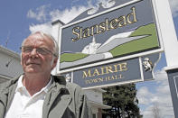 Mayor Philippe Dutil stands in front of the municipal office in Stanstead, Quebec on Friday, May 11, 2012. A Vermont wind power developer and two dairy farmers in the border community of Derby Line say they've been surprised at the level of opposition to a plan to build two turbines that has been coming from the Quebec town of Stanstead.(AP Photo/Toby Talbot)