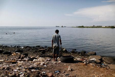 A man stands next to a pile of garbage on the shores of Lake Maracaibo in Maracaibo, Venezuela July 26, 2018. Picture taken July 26, 2018. REUTERS/Marco Bello