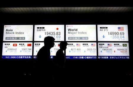 People walk past an electronic board displaying various Asian countries' stock price index and world major index outside a brokerage in Tokyo, Japan, August 21, 2015.  REUTERS/Issei Kato/File Photo
