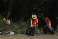 """Men clean up items left behind by migrants near a dam along the Rio Grande, where migrants, many from Haiti, had been crossing, Thursday, Sept. 23, 2021, in Del Rio, Texas. The """"amistad,"""" or friendship, that Del Rio, Texas, and Ciudad Acuña, Mexico, celebrate with a festival each year has been important in helping them deal with the challenges from a migrant camp that shut down the border bridge between the two communities for more than a week. Federal officials announced the border crossing would reopen to passenger traffic late Saturday afternoon and to cargo traffic on Monday. (AP Photo/Julio Cortez)"""