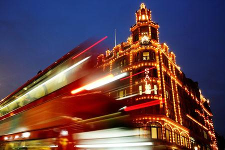 FILE PHOTO: A bus casts light trails as it passes iconic store Harrods in London, Britain January 7, 2015. REUTERS/Luke MacGregor/File Photo