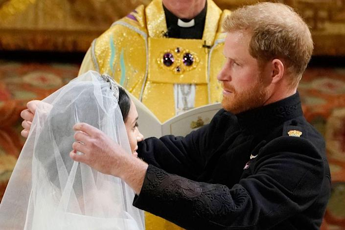 <p>Prince Harry lifts the veil over Meghan Markle's face during their wedding at St George's Chapel in Windsor.</p>