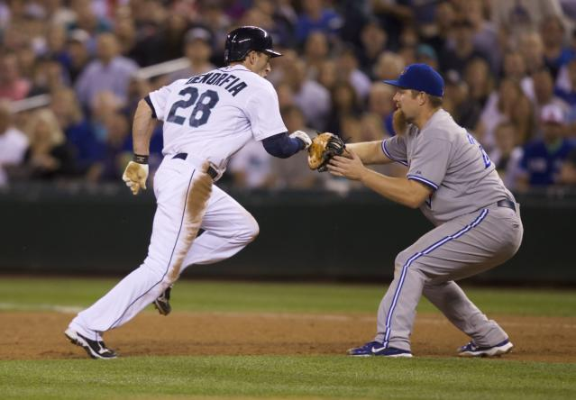 Toronto Blue Jays first baseman Adam Lind tags out Seattle Mariners' Chris Denorfia (28) in a run down after Denorfia tried to steal second base during the sixth inning of a baseball game, Wednesday, Aug. 13, 2014, in Seattle. (AP Photo/Stephen Brashear)