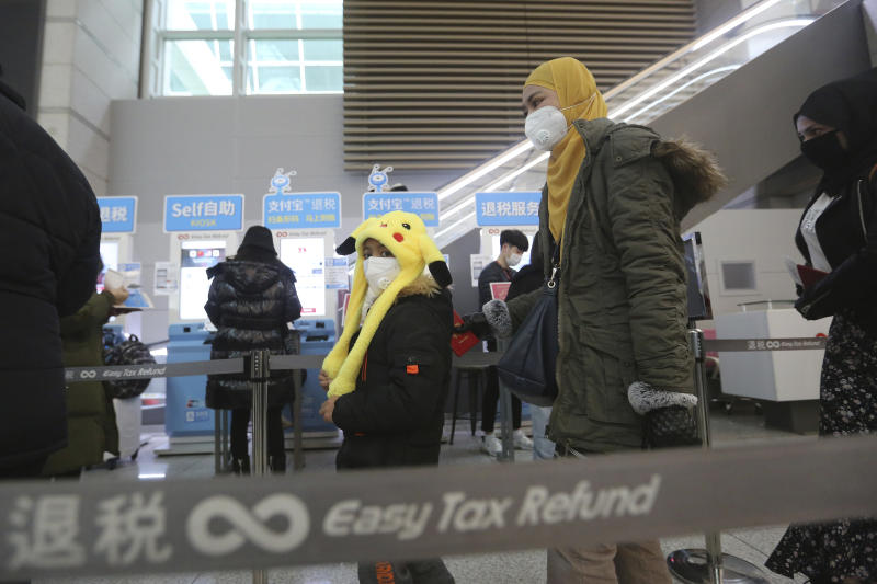 Passengers wear masks in a departure lobby at Incheon International Airport in Incheon, South Korea, Monday, Jan. 27, 2020. China on Monday expanded sweeping efforts to contain a viral disease by extending the Lunar New Year holiday to keep the public at home and avoid spreading infection. (AP Photo/Ahn Young-joon)