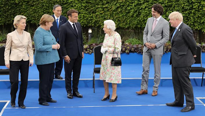 Britain's Queen Elizabeth II (5L), reacts after posing for a family photograph with, from left, President of the European Commission Ursula von der Leyen, Germany's Chancellor Angela Merkel, Japan's Prime Minister Yoshihide Suga, France's President Emmanuel Macron, Canada's Prime Minister Justin Trudeau, Britain's Prime Minister Boris Johnson, during an evening reception at The Eden Project in south west England on June 11, 2021. - G7 leaders from Canada, France, Germany, Italy, Japan, the UK and the United States meet this weekend for the first time in nearly two years, for three-day talks in Carbis Bay, Cornwall. (Photo by JACK HILL / POOL / AFP) (Photo by JACK HILL/POOL/AFP via Getty Images)