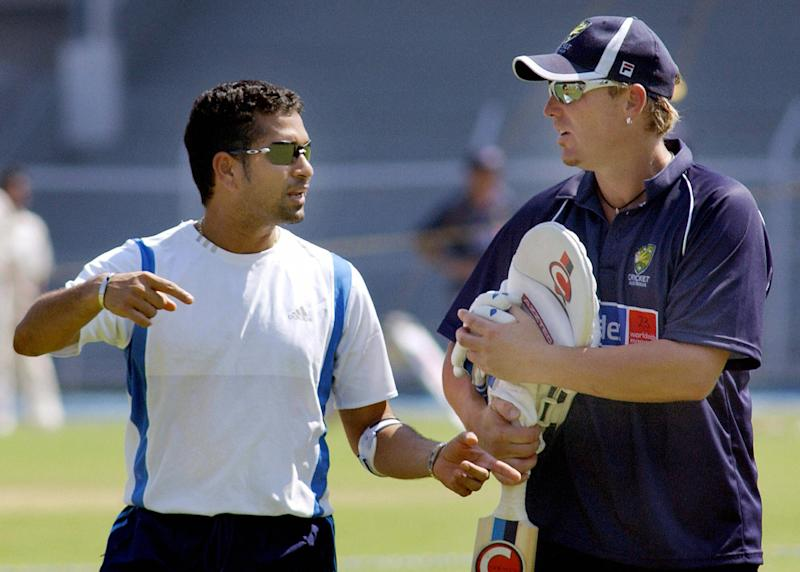 Indian batsman, Sachin Tendulkar (L) with his left arm taped because of tennis elbow, gestures towards Australian spin bowler, Shane Warne at a practice training session in Bombay, 29 September 2004. Australia open their Indian tour with a three-day match against national champions Mumbai at the Brabourne stadium on 30 September, running up to the first Test in Bangalore on 06 October and followed by Madras, Nagpur and Bombay. AFP PHOTO/Rob ELLIOTT (Photo credit should read ROB ELLIOTT/AFP via Getty Images)