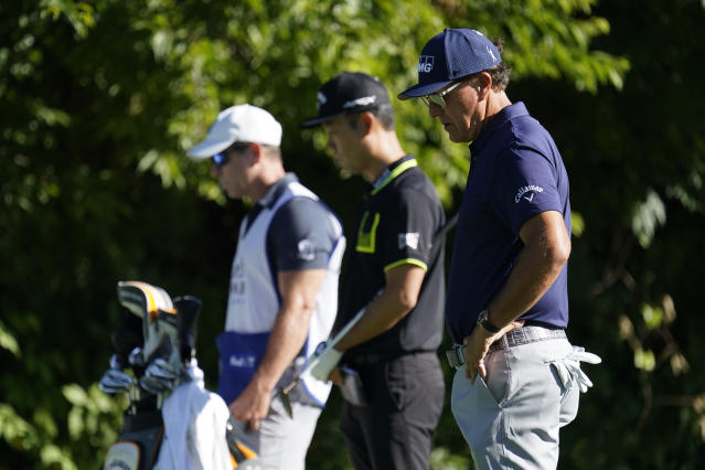 "Phil Mickelson, right, <a class=""link rapid-noclick-resp"" href=""/pga/players/3962/"" data-ylk=""slk:Kevin Na"">Kevin Na</a>, center, and their caddie observe a moment of silence on the 13th tee on Thursday. (AP Photo/David J. Phillip)"