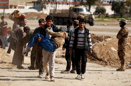 Displaced people are checked by Iraqi forces as Iraqi forces battle with Islamic State militants in western Mosul