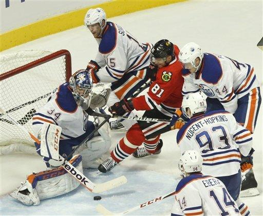 Chicago Blackhawks right wing Marian Hossa (81), from Slovakia, is unable to get his stick on the loose puck as Edmonton Oilers goalie Yann Danis gets defensive help from Nick Schultz (15) Corey Potter (44) Ryan Nugent-Hopkins (93) and Jordan Eberle during the third period of an NHL hockey game Sunday, March 10, 2013 in Chicago. The Oilers won 6-5. (AP Photo/Charles Rex Arbogast)