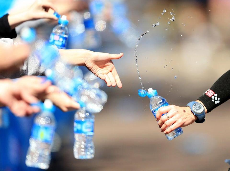 Volunteers offer runners water during the Virgin London Marathon (PA) (PA Archive)