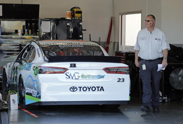 "A NASCAR official walks past the car of driver <a class=""link rapid-noclick-resp"" href=""/nascar/sprint/drivers/3534/"" data-ylk=""slk:Gray Gaulding"">Gray Gaulding</a> in the garage at Daytona International Speedway in Daytona Beach, Fla., Thursday, Feb. 15, 2018. BK Racing, which fields the car, has filed for Chapter 11 bankruptcy as it hopes to race in the Daytona 500 on Sunday. (AP Photo/Terry Renna)"