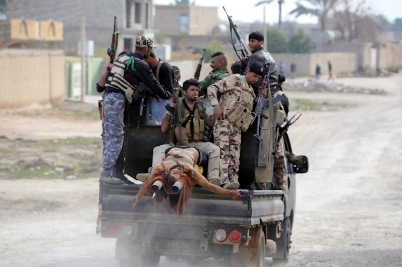 Iraqi Shiite fighters transport the body of a man, reportedly a member of the Islamic State (IS) group, after he was killed in the town of Deli Abbas, Iraq's Diyala province, in January 2015 (AFP Photo/Ahmad Al-Rubaye)