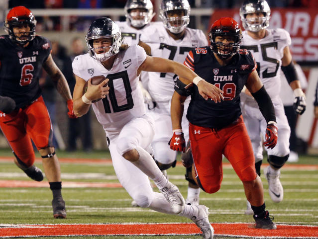 Oregon quarterback Justin Herbert (10) carries the ball as he is pursued by Utah's Bradlee Anae (6) and Pita Tonga (49) in the second half during an NCAA college football game Saturday Nov. 10, 2018, in Salt Lake City. (AP Photo/Rick Bowmer)