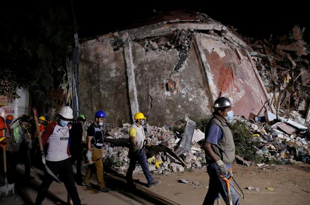 Workers walk past a collapsed building.