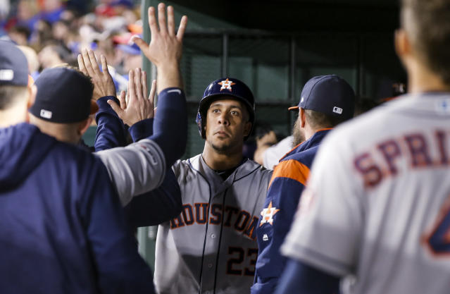 Houston Astros' Michael Brantley (23) is congratulated by teammates after scoring on a double by Carlos Correa during the fifth inning of a baseball game against the Texas Rangers, Friday, April 19, 2019, in Arlington, Texas. (AP Photo/Brandon Wade)
