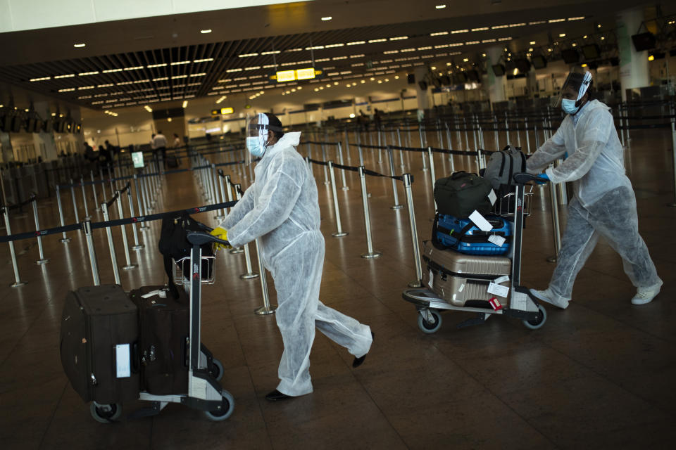 Passengers wearing full protective gear to protect against the spread of coronavirus push their luggage to a check-in counter at Zaventem international airport in Brussels. Source: AAP