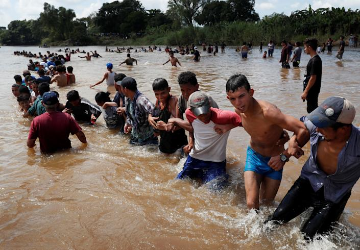 Migrants formed a human chain to pull people across a river between Guatemala and Mexico before continuing their trek toward the United States. (Photo: Leah Millis/Reuters)