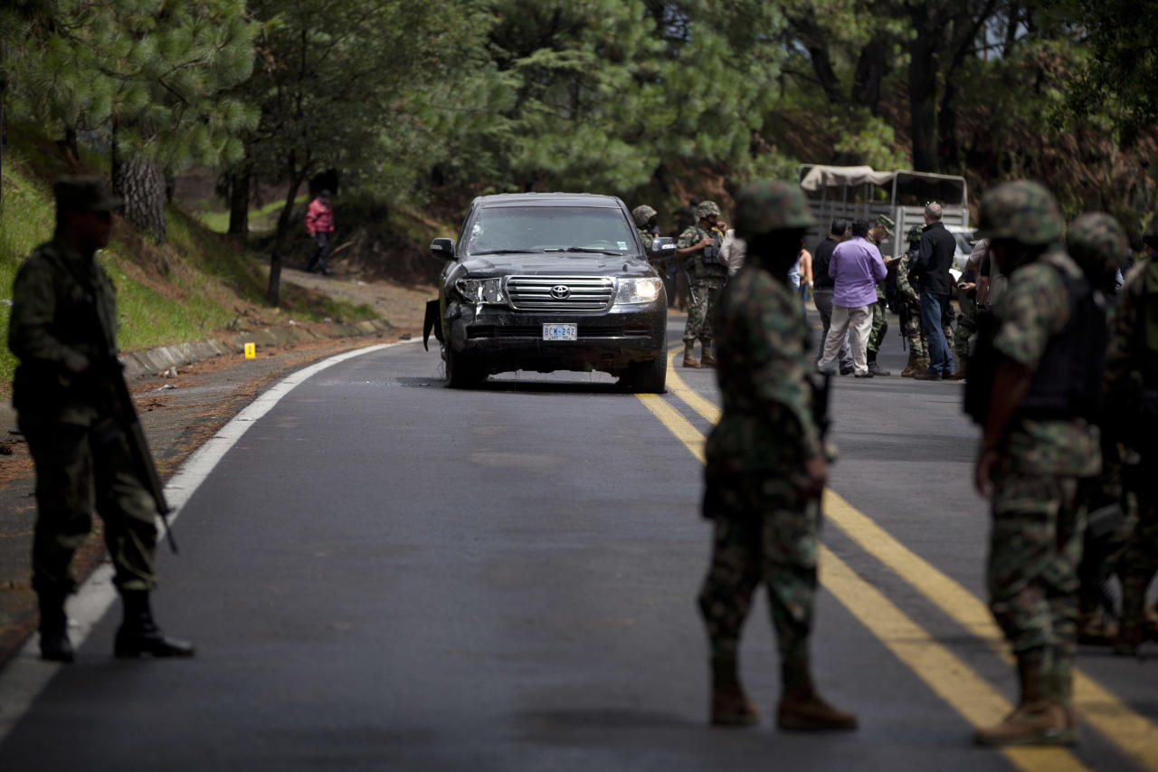 Military personal stand guard around an armored U.S. Embassy vehicle after it was attacked by unknown assailants on the highway leading to the city of Cuernavaca, near Tres Marias, Mexico, Friday, Aug. 24, 2012. Two U.S. government employees were shot and wounded in an attack on their vehicle south of Mexico City on Friday, a law enforcement official said. (AP Photo/Alexandre Meneghini)