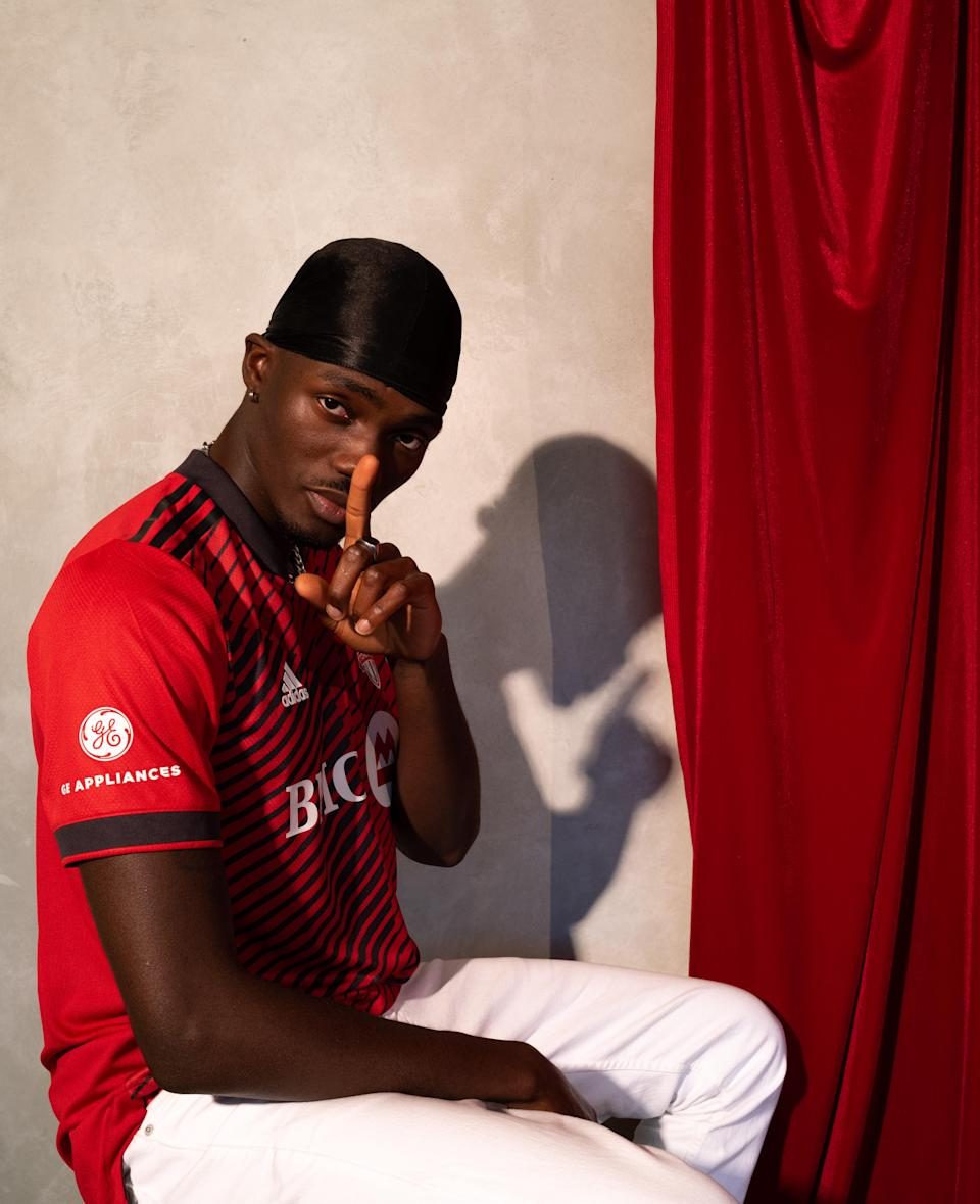 Tobi posting in a red Toronto FC jersey pointing