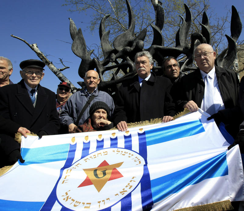"Survivors of the concentration camps,  from left Moshe Haelion,  Abraham Ashkenazi,  Zana Santicario Saatsoglou, President of Thessalonikis Jewish community  David Saltiel, and Israel Ambassador Arye Mekel hold a banner that reads in Hebrew :""The organization of death camps survivors from Greece in Israel"" in the northern port city , of Thessaloniki, Greece, on Saturday, March 16, 2013. Jewish residents in this northern Greek city have gathered to commemorate the 70th anniversary from the first roundup and deportation of Jews to Nazi extermination camps in World War II. By August 1943, 46,091 Jews had been deported to Auschwitz-Birkenau. Of those, 1,950 survived. (AP Photo/Nikolas Giakoumidis)"