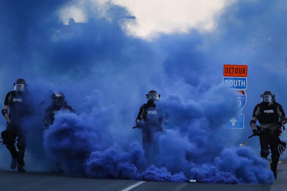 Police in riot gear walk through a cloud of blue smoke as they advance on protesters near the Minneapolis 5th Precinct, Saturday, May 30, 2020, in Minneapolis. Protests continued following the death of George Floyd, who died after being restrained by Minneapolis police officers on Memorial Day. (AP Photo/John Minchillo)