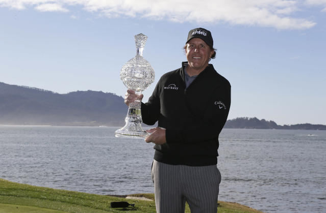 Phil Mickelson poses with his trophy on the 18th green of the Pebble Beach Golf Links after winning the AT&T Pebble Beach Pro-Am golf tournament Monday, Feb. 11, 2019, in Pebble Beach, Calif. (AP Photo/Eric Risberg)