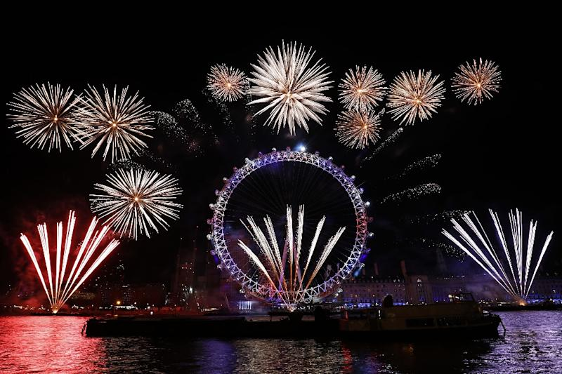 In London more than 100,000 ticket-holders watched a spectacular pyrotechnics display from the banks of the River Thames, before dancing to Auld Lang Syne (AFP Photo/Tolga AKMEN)