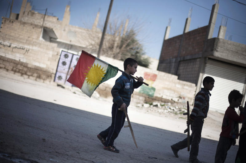FILE - In this Monday, Feb. 26, 2013 file photo, a boy carries a Kurdish flag as he and others hold toy guns on a street in Ras al-Ayn, Syria. Taking advantage of the chaos of the civil war, Syria's Kurdish minority has carved out a once unthinkable independence in their areas, creating their own police forces, even their own license plates, and exuberantly going public with their language and culture. (AP Photo/Manu Brabo, File)