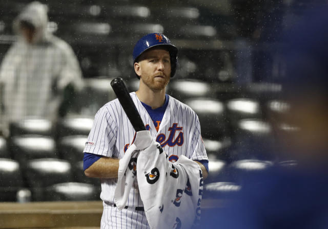 New York Mets' Todd Frazier wipes his bat with a towel as he looks for the call from his manager moments before the team's baseball game against the St. Louis Cardinals, tied 4-4, was suspended due to rain in the bottom of the ninth inning Thursday, June 13, 2019, in New York. (AP Photo/Kathy Willens)