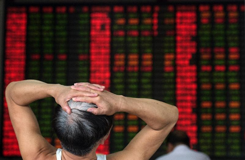 An investor reacts in front of a digital board showing stock market movements at a brokerage house in Shanghai on September 1, 2015 (AFP Photo/Johannes Eisele)