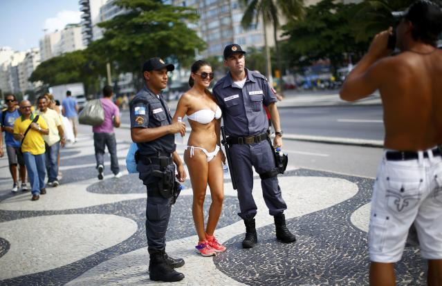 A woman poses with police officers near Copacabana Beach ahead of the 2014 World Cup in Rio de Janeiro, June 12, 2014. REUTERS/Darren Staples (BRAZIL - Tags: SOCCER SPORT SOCIETY)