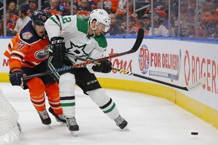 Nov 27, 2018; Edmonton, Alberta, CAN; Edmonton Oilers defensemen Oscar Klefbom (77) battles for a loose puck with Dallas Stars forward Radek Faksa (12) during the second period at Rogers Place. Mandatory Credit: Perry Nelson-USA TODAY Sports