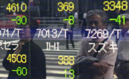 People are reflected on an electronic stock quotation board outside a brokerage in Tokyo