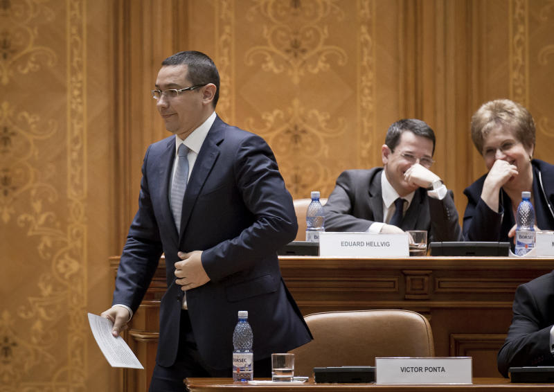 Romanian Premier designate Victor Ponta, left, prepares to address a parliament session in Bucharest, Romania, Monday, May 7, 2012. Romanian lawmakers are voting on whether to approve the prime minister designate's left-leaning Cabinet, which is expected to continue a slate of economic reforms. (AP Photo/Vadim Ghirda)