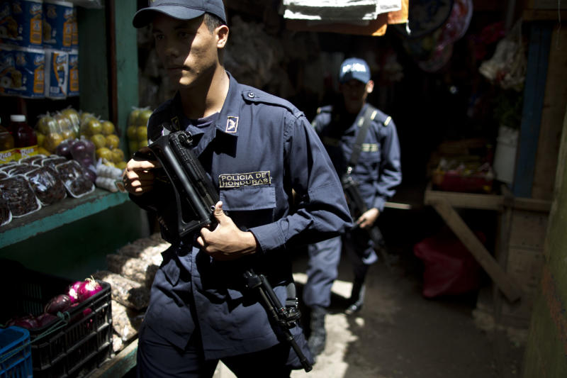 In this June 1, 2013 photo, Honduras National Police officers patrol in El Mayoreo market in Tegucigalpa, Honduras. The government of Honduras launched an unprecedented effort last year to clean up a U.S.-backed police force widely seen as deeply brutal and corrupt. One by one, hundreds of police officers were subjected to polygraph tests administered by Colombian technicians funded by the U.S. government. Nearly four of every 10 officers failed the test in the first five months it was administered, some giving answers that indicated that they had, among other violations, tortured suspects, accepted bribes and taken drugs, according to a confidential U.S. document provided to The Associated Press. (AP Photo/Esteban Felix)