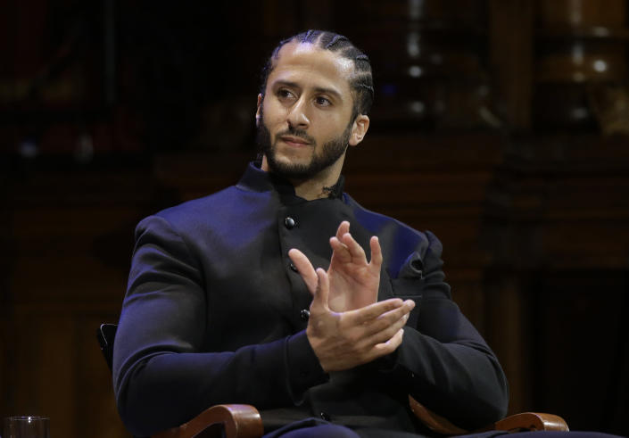 "FILE - NFL football quarterback Colin Kaepernick applauds during W.E.B. Du Bois Medal ceremonies at Harvard University in Cambridge, Mass. on Oct. 11, 2018. Kaepernick has been condemned by President Donald Trump and others on the right and had not played an NFL game since 2016, when he began kneeling during the National Anthem to protest ""a country that oppresses black people and people of color."" But he has appeared in Nike advertisements, been honored by the ACLU and Amnesty International among other organizations and reached an agreement with the Walt Disney Co. for a docuseries about this life. (AP Photo/Steven Senne, File)"