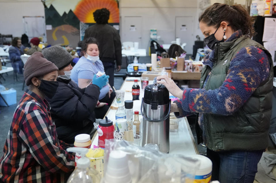 Kendra Clements, right, prepares coffee for, from left, Ruddy, Brenda and Crystal, Wednesday, Feb. 17, 2021, at the gym cafe at Tribe Gym, which has been turned into a temporary homeless shelter, in Oklahoma City. Clements and her partner Tiffany Whisman, who owns Tribe Gym, are two of several businesspeople who have opened their businesses as shelters for the homeless or people without heating during the recent severe winter weather. (AP Photo/Sue Ogrocki)