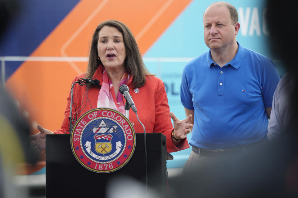 """Colorado Gov. Jared Polis, right, looks on as U.S. Rep. Diana DeGette, D-Colo., speaks during a visit to a pair of buses set up as traveling clinics as part of the state's """"Vaccines For All"""" campaign Friday, June 18, 2021, in Aurora, Colo. The buses are being used to distribute the COVID-19 vaccines. (AP Photo/David Zalubowski)"""