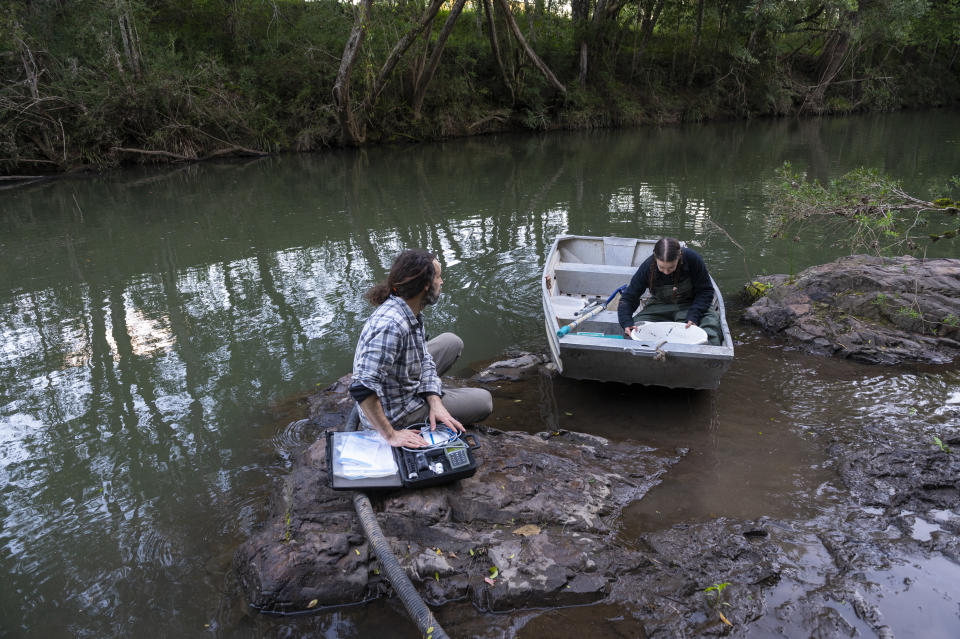 Two people searching for platypus in a river. One is in a boat.