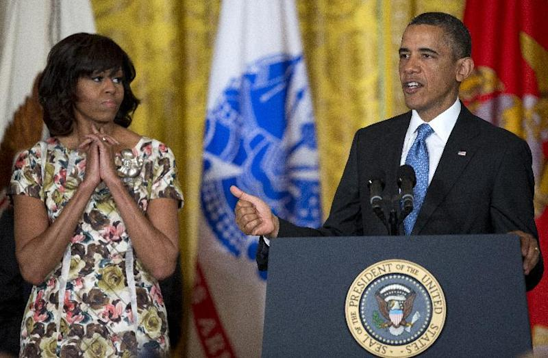 First lady Michelle Obama listens at left as President Barack Obama speaks during an event to promote hiring military veterans, Tuesday, April 30, 2013, in the East Room of the the White House in Washington. (AP Photo/Evan Vucci)