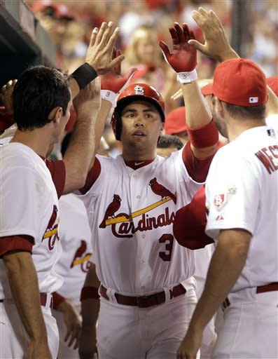 St. Louis Cardinals' Carlos Beltran, center, is congratulated by teammates Matt Carpenter, left, and Jake Westbrook after hitting a three-run home run during the third inning of a baseball game against the Pittsburgh Pirates on Wednesday, May 2, 2012, in St. Louis. Beltran also hit a three-run home run in the first inning. (AP Photo/Jeff Roberson)