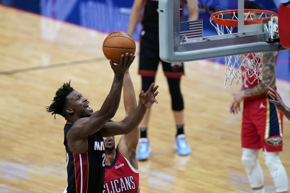 Miami Heat forward Jimmy Butler (22) goes to the basket next to New Orleans Pelicans guard Josh Hart during the first half of an NBA basketball game in New Orleans, Thursday, March 4, 2021. (AP Photo/Gerald Herbert)