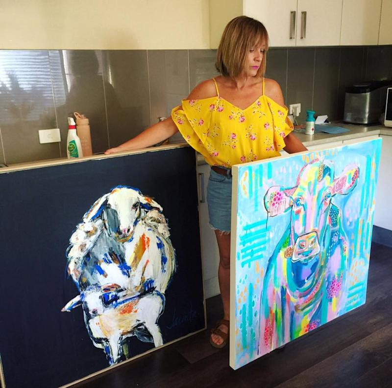 Buy from the Bush artist Jacinta Haycock poses with two canvases one of a sheep, one of a cow