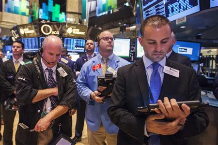 Traders pause during a moment of silence to honor victims of the 9/11 attacks on the World Trade Center, on the floor of the New York Stock Exchange September 11, 2013. REUTERS/Lucas Jackson