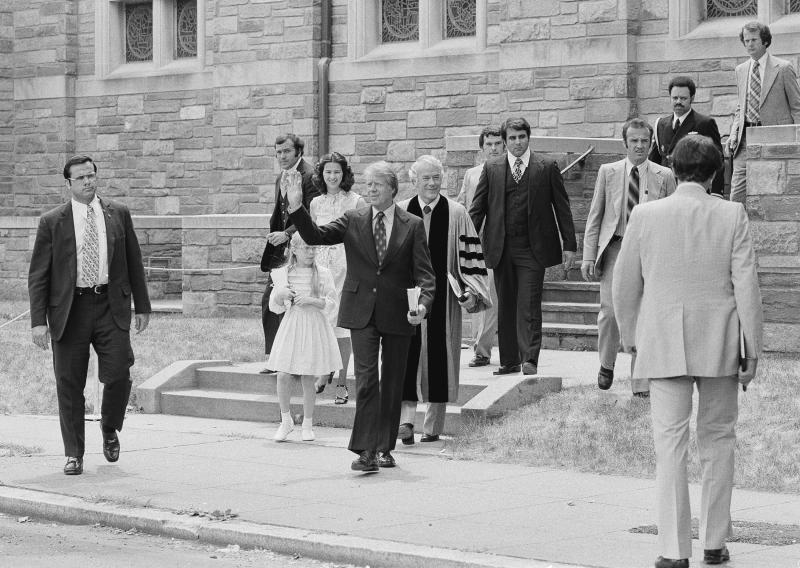 FILE - In this June 9, 1977 file photo, President Jimmy Carter waves as he departs the First Baptist Church in Washington with daughter Amy and daughter-in-law Caron Carter. The Rev. Charles Trentham, pastor of the church, is at right. At Washington churches, presidents have long been seated in the pews. Bill and Hillary Clinton favored a Methodist church. Jimmy Carter taught Baptist Sunday School. And Barack Obama dropped in at an Episcopal church next to the White House. But as Easter Sunday approaches, President Donald Trump has not attended a church service in the Capitol since the worship events during his inauguration weekend. (AP Photo, File)