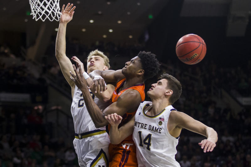 Notre Dame's Dane Goodwin, left, and Nate Laszewski (14) compete for a rebound with Virginia Tech's John Ojiako during the first half of an NCAA college basketball game Saturday, March 7, 2020, in South Bend, Ind. (AP Photo/Robert Franklin)