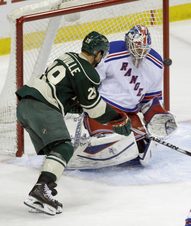 A shot on goal by Minnesota Wild's Jason Pominville, left, goes wide as New York Rangers goalie Cam Talbot defends in the first period of an NHL hockey game on Thursday, March 13, 2014, in St. Paul, Minn. (AP Photo/Jim Mone)